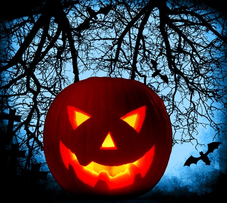 Halloween pumpkin background with glowing jack-o-lantern at night, cemetery in the dark forest