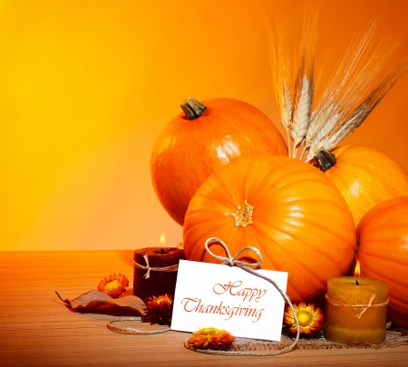 Thanksgiving holiday, pumpkin border still life decoration with candles and wheat over yellow studio light background, greeting card with text space, harvest conceptの写真素材
