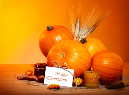 Photo for Thanksgiving holiday, pumpkin still life decoration with candles and wheat over yellow studio light background, greeting card with text space, harvest concept - Royalty Free Image