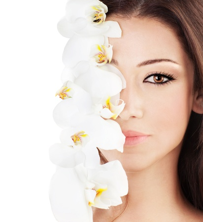 Closeup on beautiful face with white orchid flower, perfect clean skin, young female portrait,  isolated on white background with text space, beauty and spa concept