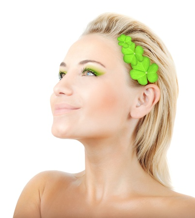 Beautiful woman with wreath of clover, fresh green plant leaves in blond hair, female face portrait isolated over white background, pretty girl with bright makeup, st. Patrick's day, spring holiday