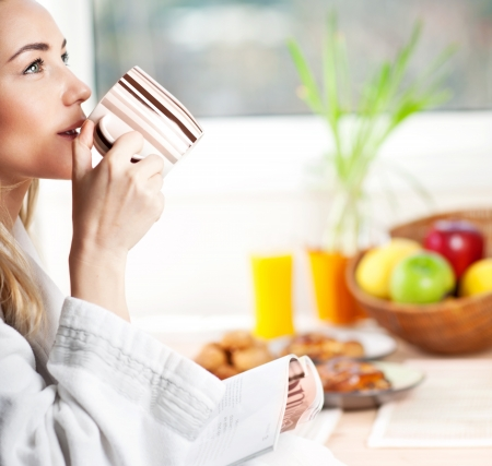 Beautiful calm young woman having morning coffee, relaxing hot drink, happy female holding cup of tea, pretty blond girl eating and drinking healthy food at home, health care and dieting concept