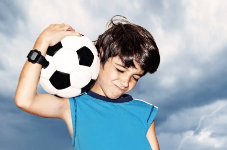 Football player celebrate victory, cute boy playing on stadium, kid enjoying team game outdoor, teen holding catching ball, happy child facial expression, sport fan portrait over cloudy sky background