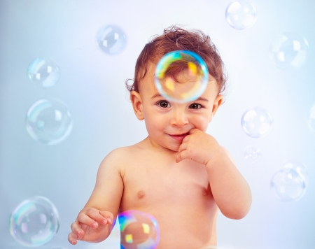 Photo pour image of cute baby boy playing with soap bubbles, closeup portrait of sweet little kid with hand near mouth isolated on blue background, adorable toddler bathe indoors, child healthcare - image libre de droit
