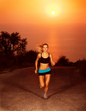 Image of of sporty blond female running along the road over sunset, slim athletic woman run in marathon, active girl doing fitness exercise outdoors, weight loss, body care, healthy lifestyle
