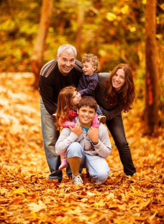 Foto de Picture of lovely family in autumn park, young parents with nice adorable kids playing outdoors, five cheerful person have fun on backyard in fall, happy family enjoy autumnal nature   - Imagen libre de derechos