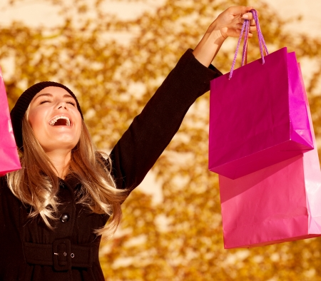 an attractive woman expressing joy of her new purchase, happy good looking girl with pink shopping bags walking in autumn park, money spending and  anti stress concept, autumnal sale