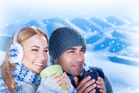 Photo pour Picture of happy couple drink hot chokolate outdoors, beautiful woman with handsome man enjoying view of mountains covered white snow and holding cups of tea in hands, loving family, Christmas time - image libre de droit