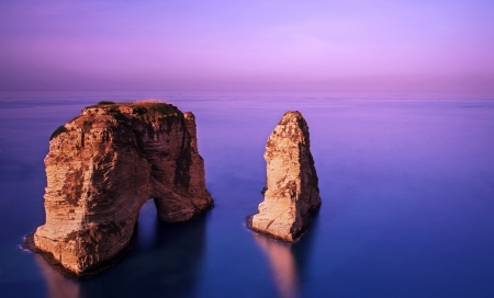 Foto de Picture of Rawsha rock on beautiful purple sunset, coastline of mediterranean sea, calm peaceful weather, famous Lebanese landmark in the water in evening, gorgeous landscape, tourism conception  - Imagen libre de derechos