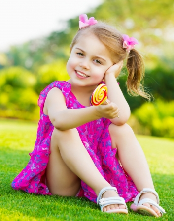 cute little girl sitting on green grass on backyard and holding in hand colorful lollipop