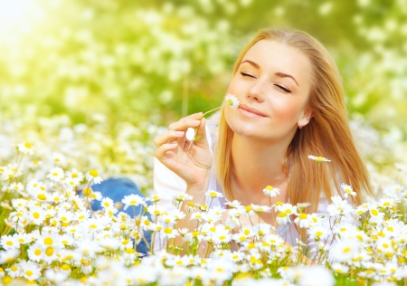 pretty blonde woman lying down in chamomile field