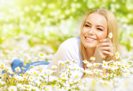 pretty woman lying down on chamomile field, happy female holding in hand beautiful white flower