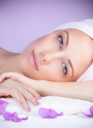 Closeup portrait of beautiful woman in spa salon laying down on massage table, enjoying dayspa, purple background, beauty treatment
