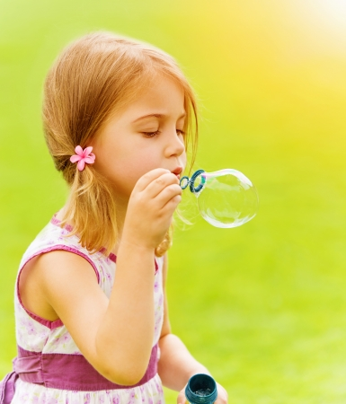 Closeup portrait of cute baby girl blowing soap bubbles in spring park, having fun outdoors, happy childhood concept