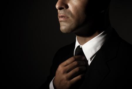 Foto de Young handsome man fixed tie isolated on black background, face part, successful businessman, mens fashion, glamour concept - Imagen libre de derechos