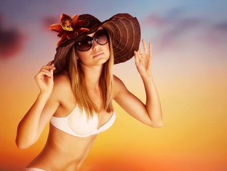 Foto de Seductive female on the beach, luxury model wearing stylish sunglasses and hat posing on beautiful orange sunset background, hot summer vacation concept - Imagen libre de derechos