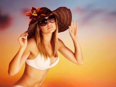 Seductive female on the beach, luxury model wearing stylish sunglasses and hat posing on beautiful orange sunset background, hot summer vacation concept