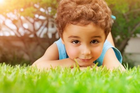 Closeup portrait of cute arabic little boy lying down on green grass field, resting outdoors on backyard, summer holidays concept