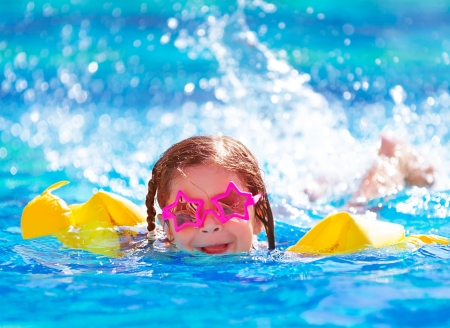 Photo pour Closeup portrait of cute little arabic girl swimming in the pool, happy child having fun in water, beach resort, summer vacation and holidays concept - image libre de droit