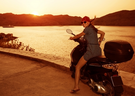 Happy prety woman on motorcycle on sunset light near sea, summer adventure, drive motorbike, active lifestyle, travel and tourism concept
