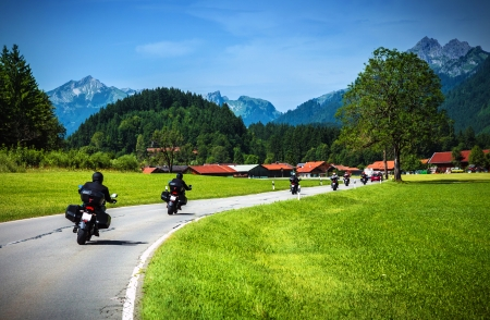 Bikers on mountainous road, touring across Alpine mountains, along little village, beautiful landscape, travel and tourism concept