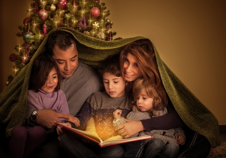 Foto de Big family reading interesting magic story in Xmas eve, happy parents with cheerful children covered with blanket, Christmas tree at home, New Year celebration - Imagen libre de derechos