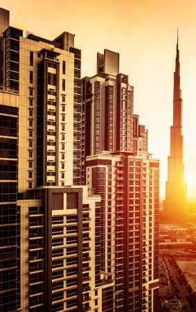 Dubai downtown in sunset, UAE, beautiful tall buildings in bright yellow sul light, burj khalifa, business centre, luxury travel and tourism concept