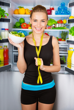 Portrait of beautiful cheerful girl holding in hand bowl with fresh tasty green salad, dietitian recommending eating vegetables, healthy organic nutrition concept