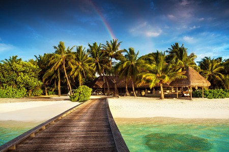 Beautiful exotic nature, wooden pier on clear turquoise water, colorful rainbow, luxury beach resort, summer vacation and holidays concept