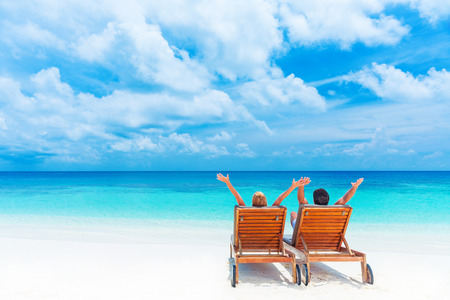 Foto de Two happy people relaxing on the beach, sitting on comfortable sunbed with raised up hands for joy, rear view, summer holidays concept     - Imagen libre de derechos