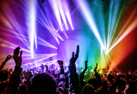 Happy young people having fun on rock concert in nightclub, colorful glowing lights, enjoying popular music, partying concept