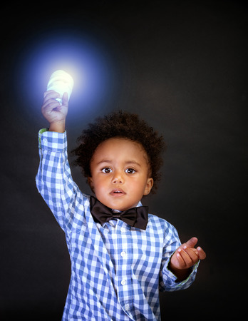 Little genius with illuminated lamp in hand isolated on black background, african boy is a great physics, back to school concept
