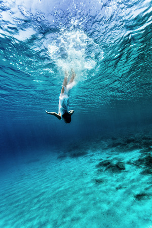 Photo for Active young female dancing underwater, enjoying summer vacation in blue transparent water, dive to the bottom of sea, enjoyment and freedom concept - Royalty Free Image