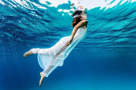 Photo pour Nice girl emerges from the sea, swimming underwater, enjoying nice refreshing water, wearing long dress, summer vacation and travel concept - image libre de droit