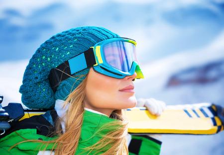 Photo pour Closeup portrait of beautiful skier girl wearing mask and holding ski, enjoying winter holidays - image libre de droit