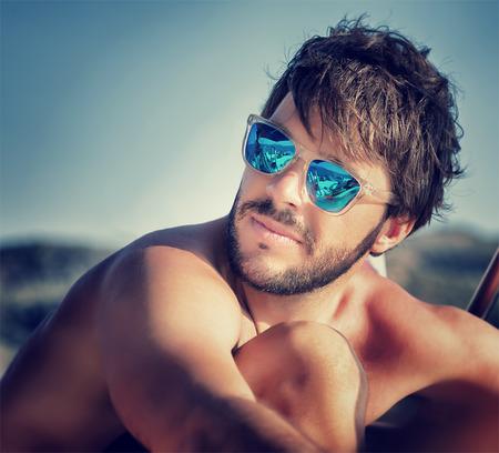 Foto de Closeup portrait of handsome man on the beach in mild sunset light, wearing blue stylish sunglasses, summer vacation concept - Imagen libre de derechos