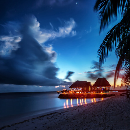 Paradise beach at night, glowing light in the restaurant over water, romantic place for honeymoon vacation, summer evening on exotic island, Maldives landscape