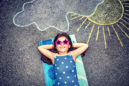 Happy little girl wearing swimsuit and stylish sunglasses lying down on the asphalt near picture of the sun comes out from behind the clouds, cute baby needs of summer holidays