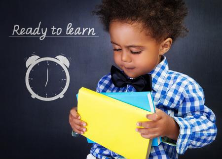 Cute african american boy with books in hands on blackboard background, adorable preschooler ready to learn in elementary school
