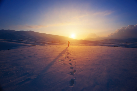 Lonely woman standing far away in bright yellow sunset light, traveling with backpack in the mountains covered with snow