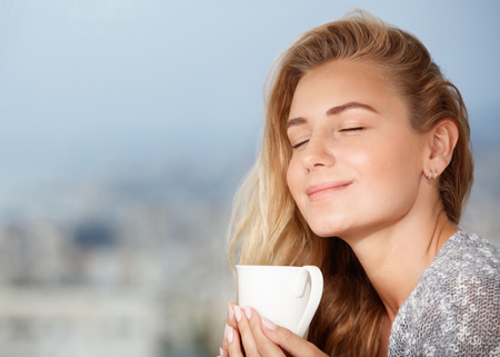 Portrait of beautiful happy girl with closed eyes, enjoying tasty strong morning coffee aroma, having breakfast in outdoor cafe