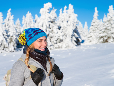 Happy woman on winter holidays in the snowy mountains, trekking with backpack along Alps, healthy active lifestyle