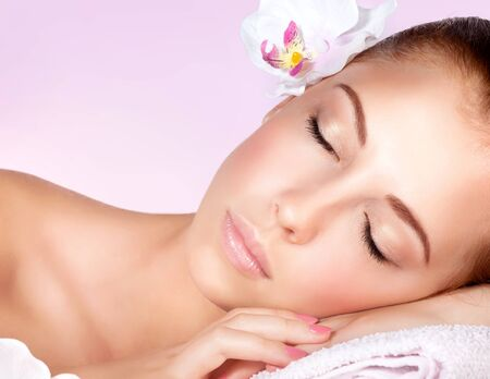 Photo pour Closeup portrait of a beautiful gentle woman with closed eyes relaxing on massage table in spa salon, healthy lifestyle, beauty treatment - image libre de droit