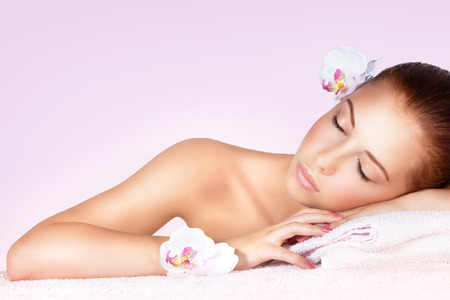 Photo pour Portrait of a beautiful gentle woman with closed eyes relaxing on massage table in spa salon, healthy lifestyle, beauty treatment - image libre de droit