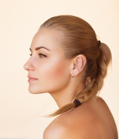 Photo pour Profile portrait of a beautiful sensual woman with braid hairstyle over beige background, gentle natural makeup, natural beauty of a woman face with a healthy skin - image libre de droit