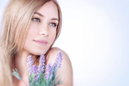 Photo pour Beautiful woman at spa, closeup portrait of a nice blond girl enjoying aroma of a lavender flowers over clear background, using natural cosmetics, healthy lifestyle - image libre de droit
