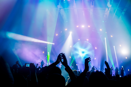 Foto de Many people enjoying concert, band performs on stage in the bright blue light, people enjoying music, dancing with raised up hands and clapping, active night life - Imagen libre de derechos