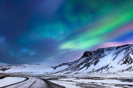 Beautiful landscape of the northern lights over hight mountains covered with snow,  Aurora Borealis, wonderful phenomena of nature, winter time in Budir, Iceland