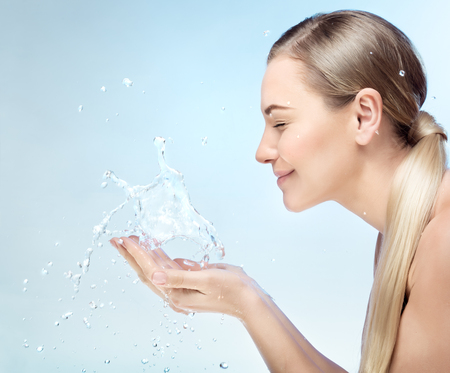 Photo for Profile portrait of a nice blond girl with pleasure washing her face in the morning by clear refreshing water, perfect clean skin, using anti acne remedy, hygiene concept  - Royalty Free Image