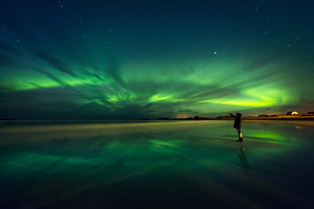 Photo pour Amazing view on the northern lights, beautiful green lights on the sky at night, traveler woman enjoying Aurora, merry dancers, beautiful phenomenon in Norway  - image libre de droit